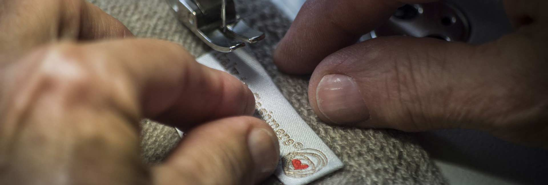 Woman's hands sewing Italy in Cashmere label
