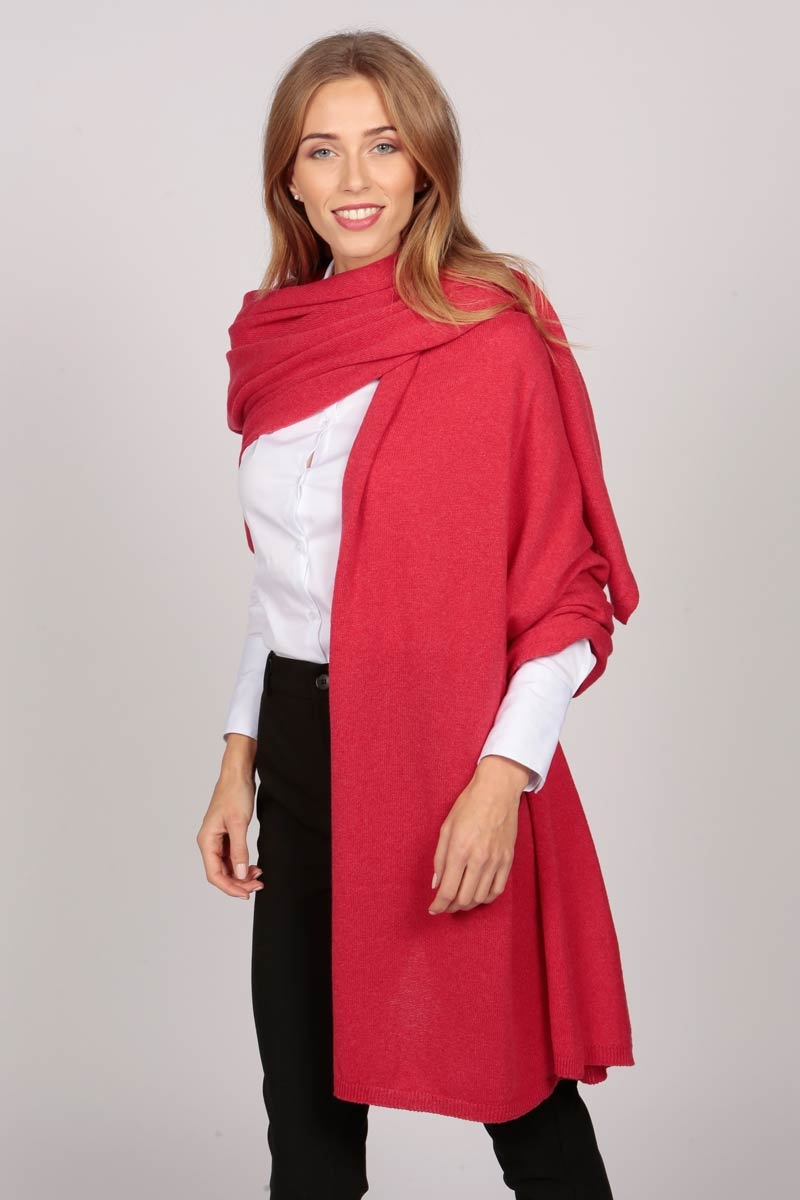A cashmere wrap in coral red worn as a single shoulder drape