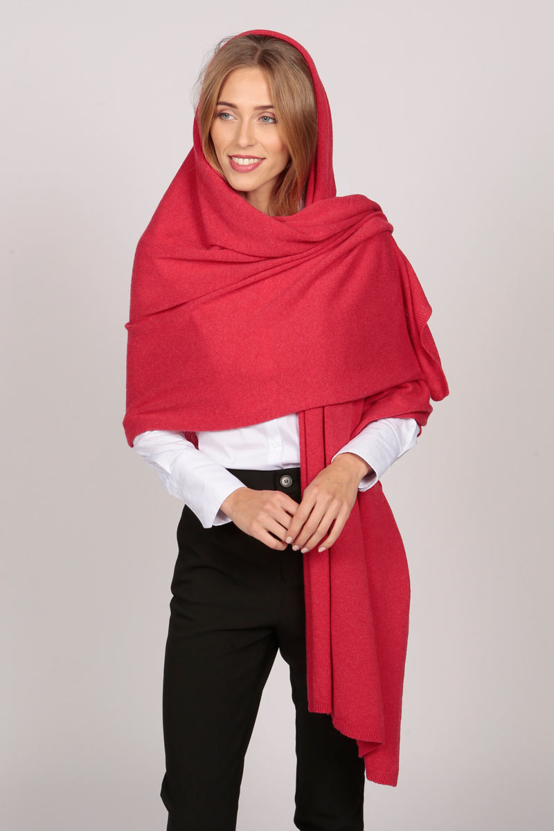 A cashmere wrap in coral red worn as an overhead drape