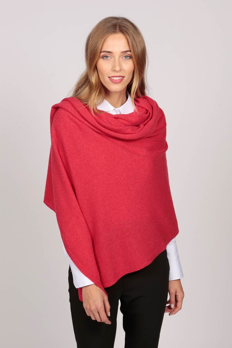 A cashmere wrap in coral red worn as a poncho