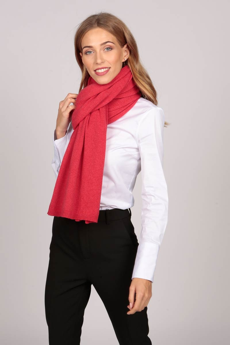 A cashmere wrap in coral red worn with a traditional knot
